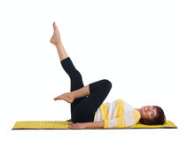 Mature woman doing gymnastics exercise. In the lying position on the back isolated on white Royalty Free Stock Photography