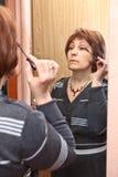 Mature woman doing make-up Stock Photo
