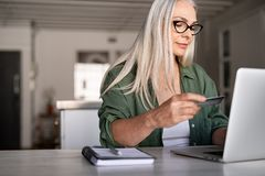 Mature woman doing online payment. Mature woman using credit card making online payment at home. Successful old woman doing online shopping using laptop. Closeup royalty free stock photography