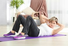 Mature woman doing sit-ups at home. Weight loss concept Stock Photo