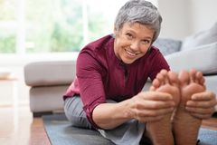 Mature woman doing stretching exercises royalty free stock photography