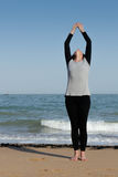 Mature woman doing the sun salutation on the beach Stock Photos