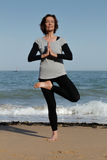Mature woman doing yoga on the beach. Mature woman doing the yoga tree pose or vrksasana on the beach Royalty Free Stock Photo