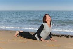 Mature woman doing yoga cobra on the beach. Mature woman doing yoga cobra or bhujangasana from the sun salutation or soorya-namaskara on the beach Royalty Free Stock Photos