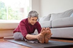 Mature woman doing yoga exercise at home royalty free stock photo