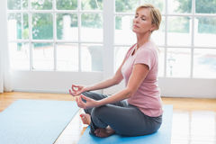 Mature woman doing yoga on fitness mat. At home in the living room Royalty Free Stock Images