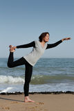 Mature woman doing yoga Lord of the Dance on the b Royalty Free Stock Photo