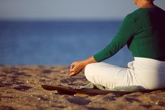 Mature woman doing yoga on sandy beach Stock Images