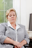 Mature woman dozing at the desk Stock Photos