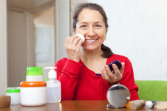 Mature woman in dress puts facepowder on  face Royalty Free Stock Photography