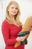 Mature Woman Drilling Wall To Hang Picture Frame Stock Image
