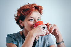 Mature woman drinking coffee Stock Images