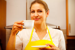 Mature woman drinking cup of coffee in kitchen. Stock Image