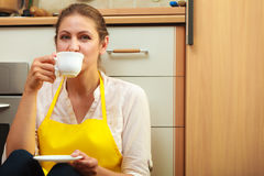 Mature woman drinking cup of coffee in kitchen. Mature woman in apron drinking cup of coffee in kitchen. Housewife female relaxing resting sitting on floor Stock Photography