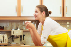 Mature woman drinking cup of coffee in kitchen. Royalty Free Stock Image