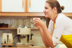 Mature woman drinking cup of coffee in kitchen. Stock Photography