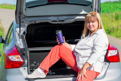 Mature woman drinking a drink sitting on the trunk Royalty Free Stock Images