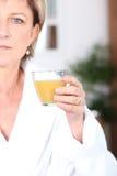 Mature woman drinking juice Royalty Free Stock Image