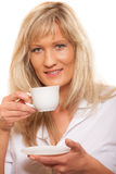 Mature woman drinking tea or coffee.. Royalty Free Stock Images