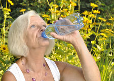 Mature woman drinking water. Stock Images