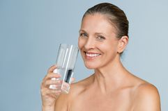 Mature woman drinking water stock photography