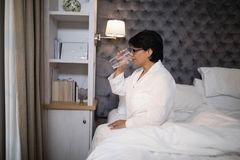 Mature woman drinking water while sitting on bed. At home Stock Images