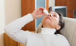 Mature woman dripping nasal drops Royalty Free Stock Photo