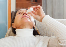Mature woman dripping nasal drops Royalty Free Stock Images