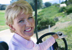 Mature woman driving golf buggy on golf course, looking over shoulder, smiling, close-up, rear view, portrait Royalty Free Stock Image