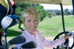 Mature woman driving golf buggy on golf course, smiling, side view, portrait Stock Photo
