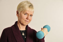 Mature woman with dumbbell Stock Images