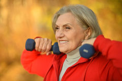 Mature woman with dumbbells Royalty Free Stock Photos