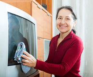 Mature woman dusting TV Stock Photo