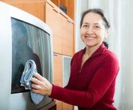 Mature woman dusting TV Stock Photo