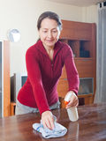 Mature  woman dusting wooden table Royalty Free Stock Photos