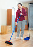 Mature woman with dustpan and brush Stock Photo