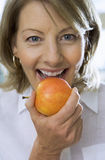 Mature woman eating apple, close-up, front view, portrait Stock Images