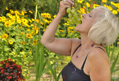Mature woman eating grapes. Royalty Free Stock Image