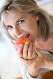 Mature woman eating red apple royalty free stock photography