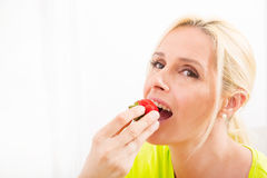 Mature woman eating strawberry Stock Images