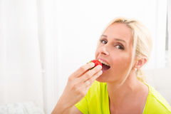 Mature woman eating strawberry Royalty Free Stock Images