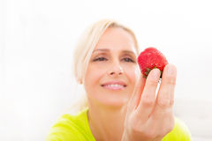 Mature woman eating strawberry Royalty Free Stock Photography