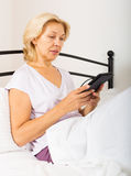 Mature woman with eBook laying in  bed Royalty Free Stock Images