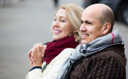 Mature woman and elderly man posing together outdoors Stock Photos