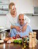 Mature woman with elderly senior preparing vegetarian food toget Royalty Free Stock Images