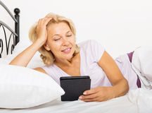 Mature woman with electronic book laying in  bed Stock Images