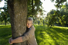 Mature woman embracing tree, eyes closed (lens flare) royalty free stock photography