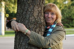 Mature woman embracing tree Stock Images
