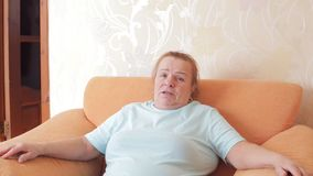 Mature woman emotionally tells something to the camera while sitting in a chair at home stock video footage