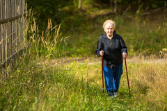 Mature woman engaged in Nordic walking outside the city. Royalty Free Stock Image